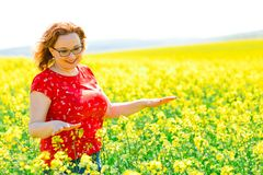Ελκυστική γυναίκα στην κόκκινη τοποθέτηση φορεμάτων στον τομέα βιασμών ελαιοσπόρων στοκ φωτογραφία με δικαίωμα ελεύθερης χρήσης