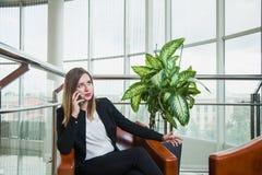 Ελκυστική γυναίκα στις μαύρες συζητήσεις κοστουμιών πέρα από το τηλέφωνο Στοκ φωτογραφία με δικαίωμα ελεύθερης χρήσης