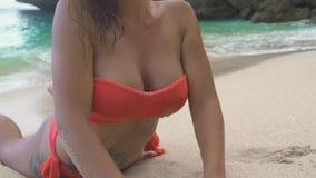 Ελκυστική γυναίκα στο μπικίνι που βρίσκεται στην αμμώδη παραλία και που χαμογελά στη κάμερα στο μπλε τοπίο θάλασσας Όμορφο πρότυπ απόθεμα βίντεο