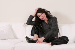 ελκυστική γυναίκα συνεδρίασης καναπέδων Στοκ Εικόνες