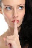Ελκυστική γυναίκα brunette που τοποθετεί το δάχτυλο μπροστά από τα χείλια της στην άσπρη ανασκόπηση Στοκ Εικόνες