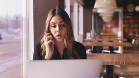 Ελκυστική επιχειρηματίας κινηματογραφήσεων σε πρώτο πλάνο στο μαύρο πουκάμισο που μιλά στο τηλέφωνο στον καφέ απόθεμα βίντεο