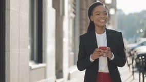 Ελκυστική επιχειρηματίας που χρησιμοποιεί το smartphone που περπατά στην οδό κοντά στο επιχειρησιακό κέντρο Μαύρος μοντέρνος drea απόθεμα βίντεο