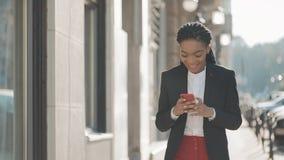 Ελκυστική επιχειρηματίας που χρησιμοποιεί το smartphone που περπατά στην οδό κοντά στο επιχειρησιακό κέντρο Μαύρος μοντέρνος drea φιλμ μικρού μήκους