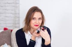 Ελκυστική επιχειρησιακή γυναίκα που βάζει το κόκκινο κραγιόν που εξετάζει τη κάμερα με το χαμόγελο Στοκ Εικόνα