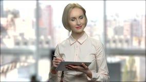 Ελκυστική επιχειρησιακή γυναίκα που εργάζεται στην ταμπλέτα PC απόθεμα βίντεο