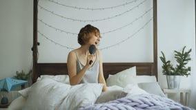 Ελκυστική εύθυμη γυναίκα που χορεύει και που τραγουδά με τη χτένα όπως τη συνεδρίαση μικροφώνων στο κρεβάτι στο σπίτι φιλμ μικρού μήκους
