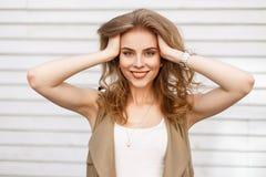 Ελκυστική εύθυμη νέα γυναίκα σε ένα κομψό θερινό μπεζ γιλέκο σε μια άσπρη μοντέρνη τοποθέτηση μπλουζών στοκ εικόνες