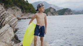 Ελκυστική θάλασσα προσοχής αγοριών και στάση σε έναν απότομο βράχο με το διογκώσιμο κύκλο Ένα μικρό αγόρι που στέκεται στο βράχο  απόθεμα βίντεο