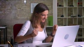 Ελκυστική θηλυκή συνεδρίαση εργαζομένων γραφείων μπροστά από το lap-top που παίρνει συγκινημένο πέρα από τις καλές ειδήσεις και π απόθεμα βίντεο