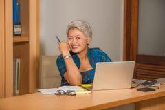 Ελκυστική και ευτυχής επιτυχής μέση ηλικίας ασιατική γυναίκα που εργάζεται στο γραφείο φορητών προσωπικών υπολογιστών που χαμογελ στοκ φωτογραφία με δικαίωμα ελεύθερης χρήσης