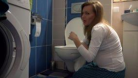 Ελκυστική καλή έγκυος γυναίκα που γονατίζει κάτω και που κάνει εμετό στην τουαλέτα φιλμ μικρού μήκους