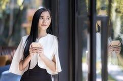 ελκυστική καυκάσια επιχειρηματίας που χρησιμοποιεί το smartphone κοντά στο γυαλί W Στοκ φωτογραφία με δικαίωμα ελεύθερης χρήσης