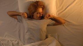 Ελκυστική κυρία που χασμουριέται και που τεντώνει στο κρεβάτι, που χαιρετά τη νέα ημέρα με το χαμόγελο απόθεμα βίντεο