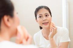 Ελκυστική λεπτή γυναίκα που χρησιμοποιεί το καλλυντικό σφουγγάρι makeup Στοκ Φωτογραφία