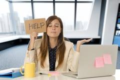 Ελκυστική λυπημένη και απελπισμένη επιχειρησιακή γυναίκα που υφίσταται την πίεση στο σημάδι βοήθειας εκμετάλλευσης γραφείων φορητ Στοκ Εικόνες