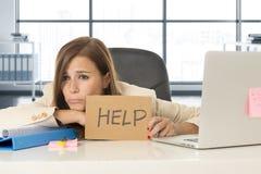 Ελκυστική λυπημένη και απελπισμένη επιχειρησιακή γυναίκα που υφίσταται την πίεση στο σημάδι βοήθειας εκμετάλλευσης γραφείων φορητ Στοκ φωτογραφία με δικαίωμα ελεύθερης χρήσης