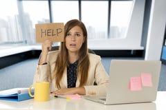 Ελκυστική λυπημένη και απελπισμένη επιχειρησιακή γυναίκα που υφίσταται την πίεση στο σημάδι βοήθειας εκμετάλλευσης γραφείων φορητ Στοκ εικόνες με δικαίωμα ελεύθερης χρήσης