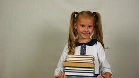Ελκυστική μαθήτρια που κρατά έναν σωρό των βιβλίων Πορτρέτο του παιδιού σχολείου σε ομοιόμορφο απόθεμα βίντεο