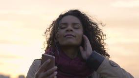 Ελκυστική μικτή γυναίκα φυλών που ακούει τη μουσική, που χορεύει στη έκσταση στο ηλιοβασίλεμα απόθεμα βίντεο