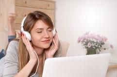 Ελκυστική μουσική ακούσματος γυναικών στον καναπέ Στοκ φωτογραφία με δικαίωμα ελεύθερης χρήσης
