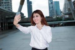 Ελκυστική νέα ασιατική γυναίκα που παίρνει μια φωτογραφία selfie στο αστικό υπόβαθρο πόλεων στοκ εικόνα με δικαίωμα ελεύθερης χρήσης