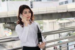 Ελκυστική νέα ασιατική επιχειρησιακή γυναίκα που μιλά στο κινητό έξυπνο τηλέφωνο και που διοργανώνει το φάκελλο εγγράφων στο εξωτ στοκ εικόνα