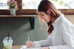 Ελκυστική νέα ασιατική σημείωση γραψίματος επιχειρησιακών γυναικών για το γραφείο στην αρχή στοκ εικόνα με δικαίωμα ελεύθερης χρήσης