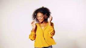 Ελκυστική νέα γυναίκα αφροαμερικάνων που ακούει τη μουσική με τα ακουστικά και που χορεύει στο άσπρο υπόβαθρο τοίχων κορίτσι μέσα απόθεμα βίντεο