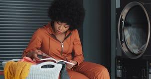 Ελκυστική νέα γυναίκα αφροαμερικάνων που διαβάζει ένα βιβλίο πλένοντας το πλυντήριό της laundromat φιλμ μικρού μήκους