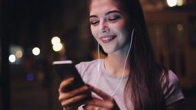 Ελκυστική νέα νέα γυναίκα γυναικών με τα ακουστικά στα αυτιά της που ακούνε τη μουσική και που χρησιμοποιούν το smartphone Θολωμέ απόθεμα βίντεο