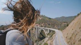 Ελκυστική νέα γυναίκα με την πετώντας τρίχα που εξετάζει τη κάμερα στο καταπληκτικό ηλιόλουστο vista σημείο στη γέφυρα κολπίσκου  φιλμ μικρού μήκους