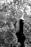 Ελκυστική νέα γυναίκα με τη μακροχρόνια όμορφη τοποθέτηση χαμόγελου τρίχας υπαίθρια Μαύρη, άσπρη φωτογραφία Στοκ Φωτογραφίες