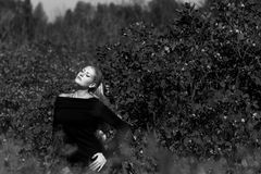 Ελκυστική νέα γυναίκα με τη μακροχρόνια όμορφη τοποθέτηση χαμόγελου τρίχας υπαίθρια Μαύρη, άσπρη φωτογραφία Στοκ Εικόνες