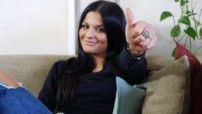 Ελκυστική νέα γυναίκα με τον αντίχειρα που κάνει επάνω το ΕΝΤΑΞΕΙ σημάδι Στοκ Φωτογραφίες