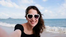 Ελκυστική νέα γυναίκα που έχει την τηλεοπτική συνομιλία χρησιμοποιώντας το smartphone και λέγοντας γειά σου hion την παραλία Νέα  απόθεμα βίντεο