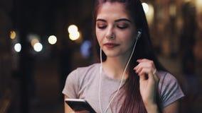 Ελκυστική νέα γυναίκα που ακούει τη μουσική στο έξυπνο τηλέφωνο υπαίθρια το βράδυ Πορτρέτο του χαμογελώντας κοριτσιού που στέκετα απόθεμα βίντεο