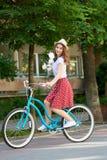 Ελκυστική νέα γυναίκα που απολαμβάνει οδηγώντας το ποδήλατό της στοκ εικόνα