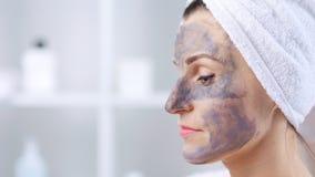 Ελκυστική νέα γυναίκα που βάζει την γκρίζα μάσκα αργίλου στο πρόσωπό της με spatula απόθεμα βίντεο