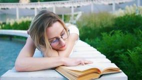 Ελκυστική νέα γυναίκα που βρίσκεται διαβάζοντας ένα βιβλίο στον αστικό κήπο απόθεμα βίντεο