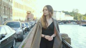 Ελκυστική νέα γυναίκα που περιμένει κάποιο στην οδό, που στέκεται στη γέφυρα απόθεμα βίντεο