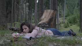Ελκυστική νέα γυναίκα που στηρίζεται κάτω από τη χλόη στα ξύλα που απολαμβάνουν τη σιωπή και τη φύση που παίρνουν ένα σπάσιμο από απόθεμα βίντεο