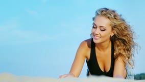 Ελκυστική νέα γυναίκα που στηρίζεται στην παραλία Το παιχνίδι βρίσκεται ενάντια στον ουρανό απόθεμα βίντεο
