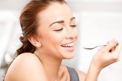 Ελκυστική νέα γυναίκα που τρώει το γιαούρτι Στοκ Φωτογραφία