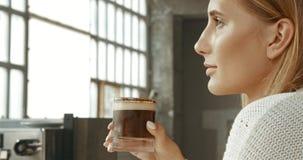 Ελκυστική νέα γυναίκα που φορά ένα άσπρο πουλόβερ σε ένα αρτοποιείο ύφους σοφιτών ή τη καφετερία με έναν πάγο latte Στοκ Φωτογραφίες