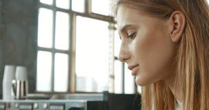 Ελκυστική νέα γυναίκα που φορά ένα άσπρο πουλόβερ σε ένα αρτοποιείο ύφους σοφιτών ή τη καφετερία με έναν πάγο latte Στοκ εικόνες με δικαίωμα ελεύθερης χρήσης