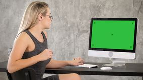 Ελκυστική νέα γυναίκα που φορά τα γυαλιά που μιλούν στη κάμερα Πράσινη επίδειξη προτύπων οθόνης απόθεμα βίντεο