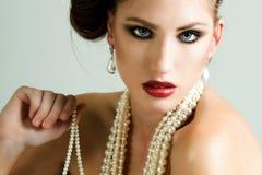 Ελκυστική νέα γυναίκα που φορά τα μαργαριτάρια Στοκ Φωτογραφία