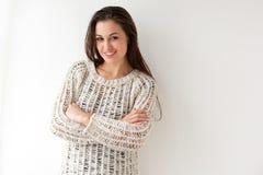 Ελκυστική νέα γυναίκα που χαμογελά με τα όπλα που διασχίζονται ενάντια στο άσπρο backgorund στοκ φωτογραφίες