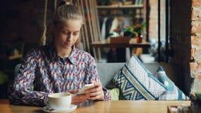 Ελκυστική νέα γυναίκα που χρησιμοποιεί το σύγχρονο smartphone στη καφετερία σχετικά με την οθόνη φιλμ μικρού μήκους